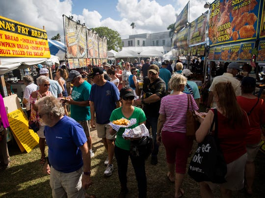 People walk through the food booth area at the annual Everglades Seafood Festival in Everglades City on Saturday, Feb. 10, 2018.