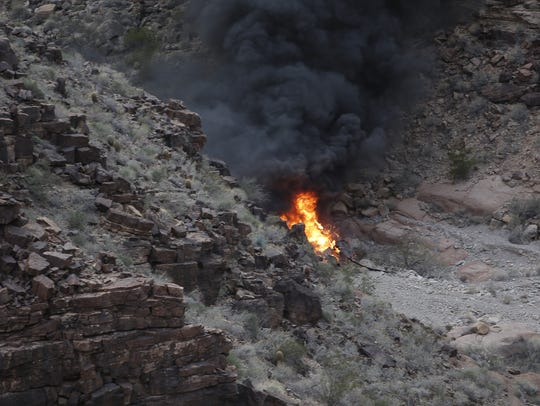 A crashed helicopter burns in a remote section of the