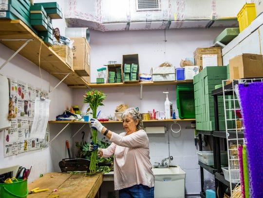 Floral designer Mary Craig works on floral arrangements