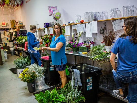 Owner Thea Cernohous, center, works on floral arrangements for Valentine's Day in the back of Petals & Presents Florist in Estero on Monday, Feb. 13, 2018.