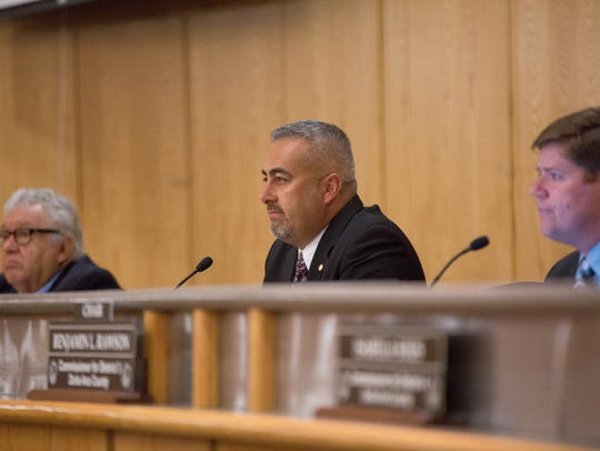 John Vasquez, county commissioner for district 5, listens