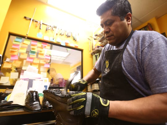 Refugio Contreras, owner of C&F Shoe Repair hammers a sole to a hiking boot in the City of Poughkeepsie on Friday, Feb. 9, 2018.