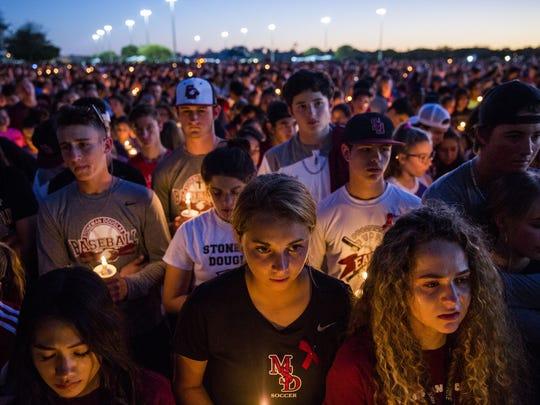 People mourn during a candlelight vigil at Pine Trails