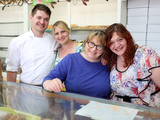 Toni Plazarin, second from right, with her children, Danny Plazarin, left, Lorrie Plazarin and Becky Brown at the orginal Holtman's in Loveland that Toni's father, Charles Holtman opened in 1960. Toni's children all work for Holtman's. Photo shot Monday May 4, 2015. The Enquirer/Cara Owsley