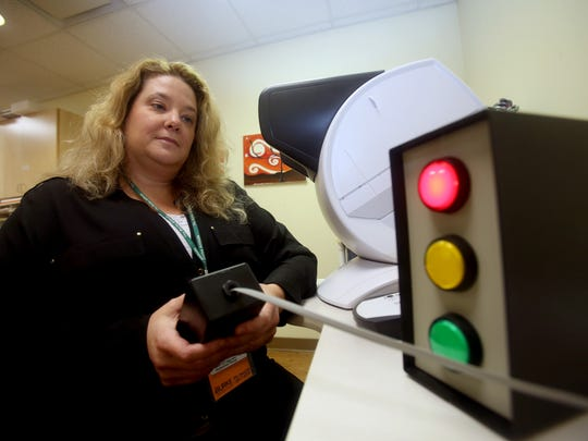 Andrea Sullivan, Occupational Therapy Supervisor for Outpatient Services at Burke Rehabilitation Hospital in White Plains, demonstrates a device used to measure driver's reaction times Feb. 23, 2018. Sullivan's department evaluates elderly drivers to measure if they're abilities have deteriorated. Drivers who have experienced physical issues such as strokes are also evaluated.