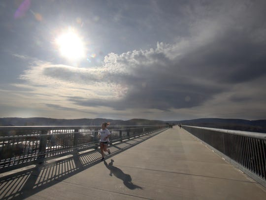 A runner makes her way over the Walkway Over the Hudson