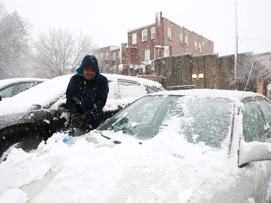 Miguel Mendoza clears the snow from his car in the