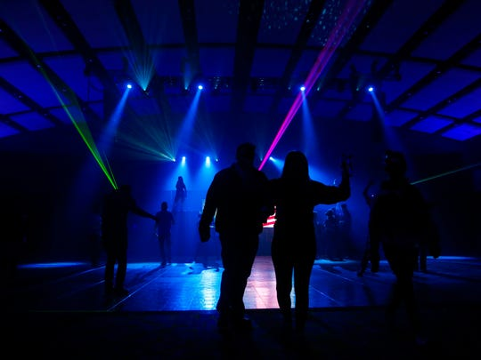 Attendees dance in club sizzle during the 11th annual Blue Ribbon Bacon Festival at the Iowa Events Center Saturday, Feb. 17, 2018.