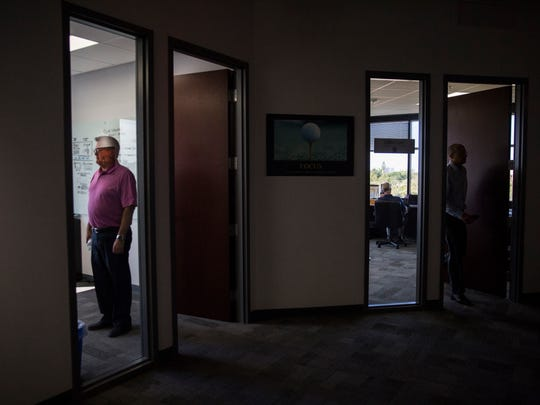 Golf Life Navigators employees walk in and out of their office spaces at The Rocket Lounge on Tuesday, March 6, 2018.