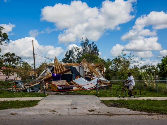A man rides his bike by a trailer that was destroyed