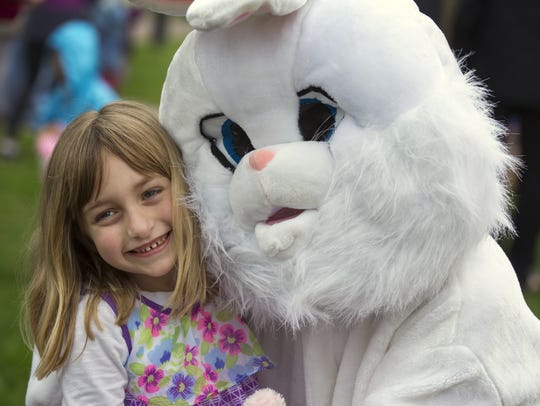 Abby Machon, 6, of Maineville, gets some picture time with the Easter Bunny at a 2017 egg hunt in Montgomery Park.