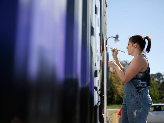 Kollet Probst works on a mural at Junction at Monroe Thursday, March 15, 2018. Probst, a working artist and mother of two, has been clean for three years following a long struggle with addiction.