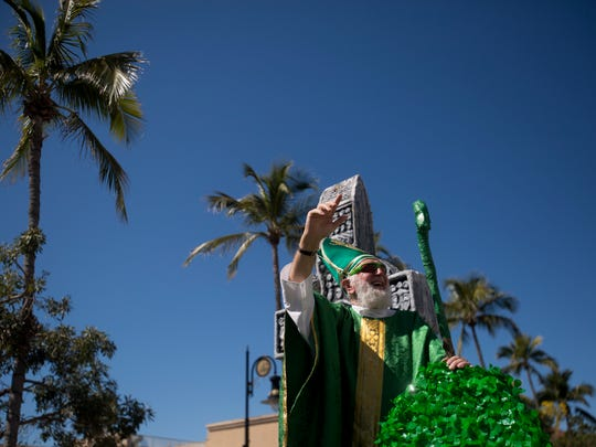 St. Patrick himself waves to the thousands of onlookers during the annual St. Patrick's Day Parade along 5th Avenue South Saturday, March 17, 2018 in Naples.