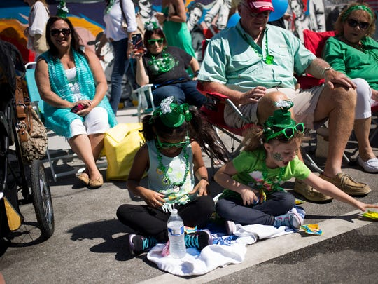 Gianna Torres, 7, left, and her cousin Izabella McClain, 6, quickly scoop up candy that was thrown their way during the annual St. Patrick's Day Parade along 5th Avenue South Saturday, March 17, 2018 in Naples.