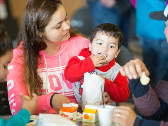 Derek Trigo, 2, eats some popcorn with his mom, Nancy, on March 17 during Soles 4 Souls Distribution Day at Mesilla Park Community Church.