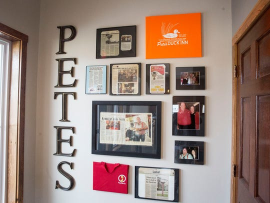 A wall of news articles and old photographs pays homage