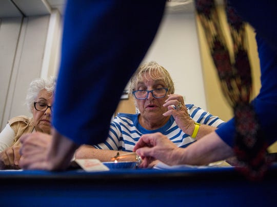 Marlene Zielinski, left, and Linda Amos, right, get help with their designs during the pysanky egg decorating workshop at the South Regional Library on Friday, March 16, 2018.
