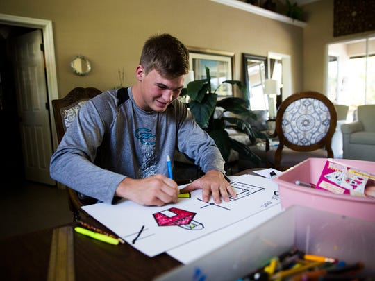 Jimmy Craig, a senior at Gulf Coast High School, makes a sign for himself and for his mother for the 'March for Our Lives' in Washington D.C. on Thursday, March 22, 2018 in his home in North Naples. Craig will be traveling to the capitol on Friday after school to attend the march with his mother.