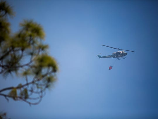 A Collier County Sheriff helicopter transports water