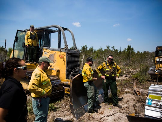 Forest rangers work on a broken down dozer by the Greenway Fire in Picayune Strand State Forest on Monday, March 26, 2018.