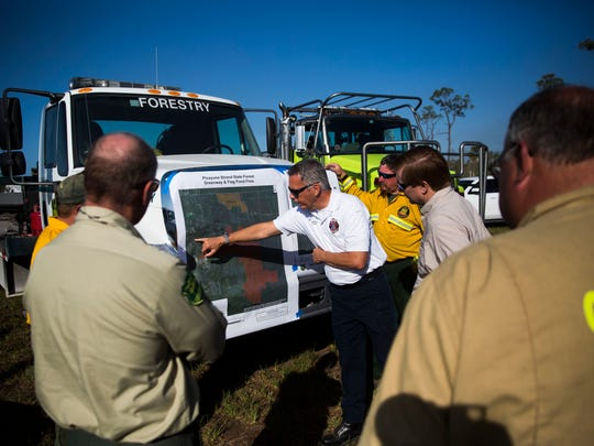 Fire Cheif Kingman Schuldt goes over the map of the Greenway fire on Wednesday, March 28, 2018 at the command post on Sabal Palm Road in Naples. The Greenway brush fire is currently 16,876 acres and remains 50 percent contained.