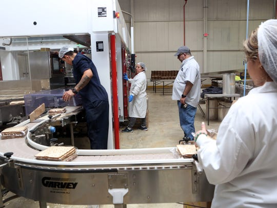 Workers package matzo as it moves along the production