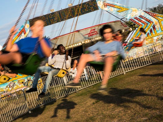 Sander Germeil, 15, second from left, smiles as he rides the swings with his friends during the 10th Annual Cornerstone Strawberry & Music Festival at Cornerstone Methodist Church in North Naples on Friday, March 2, 2018.