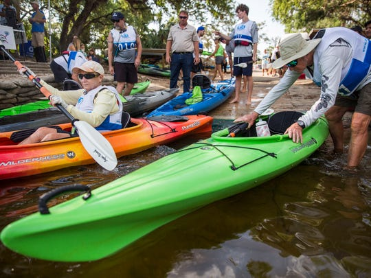 Tracy Simon, left, and Tim Simon, right, get into their kayaks during the 3rd annual Calusa Palooza at the Estero River in Koreshan State Park on Saturday, April 7, 2018.