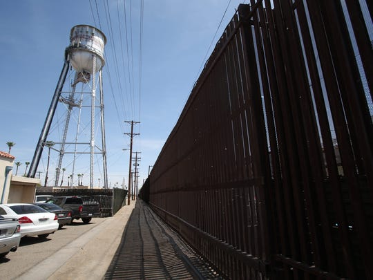Vehicles are seen parked at the border wall in downtown