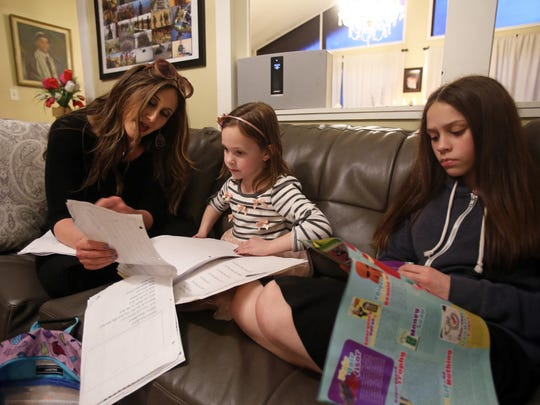 After lighting the Shabbos candles, Bassie Friedman sits with her daughters Devorah Leah Friedman, 6, and Aliza Leverton, 14, Feb. 16, 2018 in Pomona.
