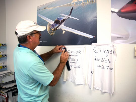 Rick Robinson, Sailor's dad, staples Sailor's shirt to the wall, commemorating the teen's first solo flight on Wednesday, May 2, 2018, at Naples Municipal Airport.