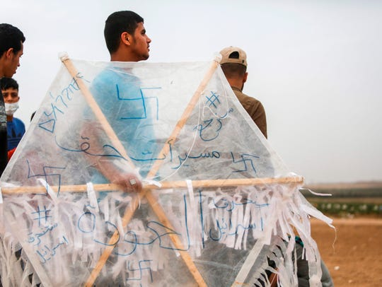 A Palestinian carries a kite before flying it over