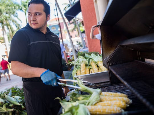 Juan Gallegos grills corn that the Florida Culinary Accelerator booth gave away for free during the 34th annual Taste of Collier at Bayfront Place on Sunday, May 6, 2018.