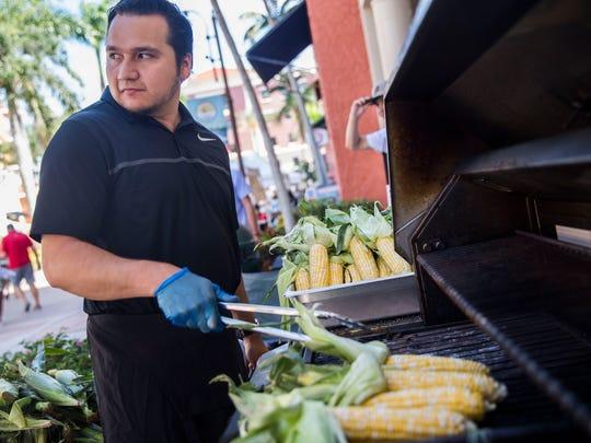 Juan Gallegos grills corn that the Florida Culinary