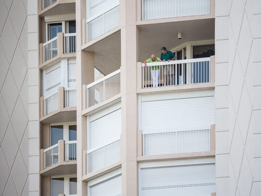 Club Brittany residents look down from their balcony are the crime scene area below them in Naples, Fla. on Wednesday, May 9, 2018.