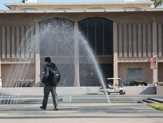 A student walks by the fountain on the campus of College