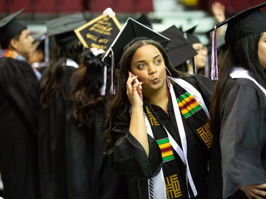 New Mexico State University graduate Kennedy Simmons looks for her loved ones on Saturday, May 12, 2018, during NMSU's commencement at the Pan American Center.