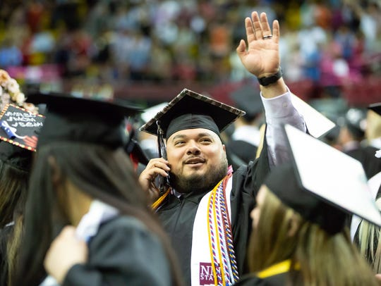 New Mexico State University graduate Daniel Hurtado waves to his loved ones on Saturday, May 12, 2018, during NMSU's commencement at the Pan American Center.