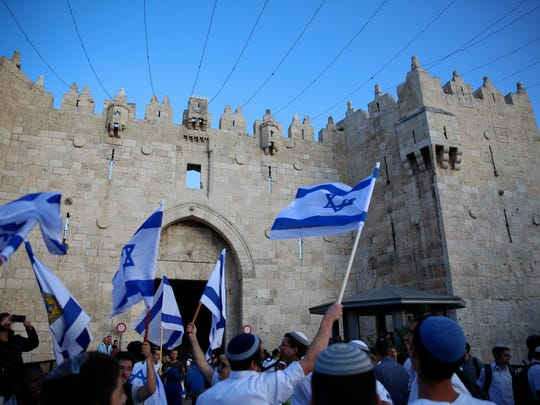 Israelis wave national flags outside the Old City's Damascus Gate, in Jerusalem, Sunday, May 13, 2018. Israel is marking the 51st anniversary of its capture of east Jerusalem in the 1967 Middle East war.