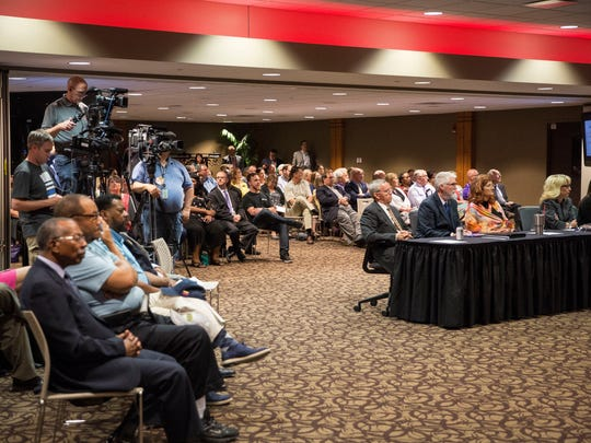 Members of the public attend a board of trustees meeting