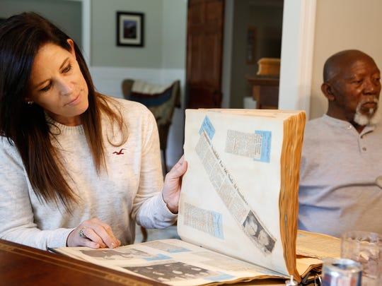 Scout Ganim, 48, granddaughter of late Florida Supreme Court Justice B.K. Roberts, looks through an old album of newspaper clippings that featured her grandfather. On the right is Charlie Hill, long-time employee of B.K.  and Mary Roberts.