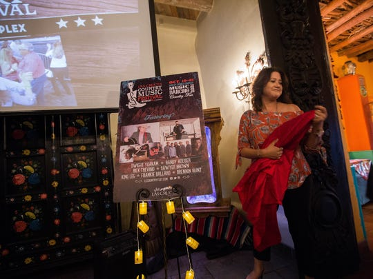 Rochelle Miller- Hernandez, tourism manager for Visit Las Cruces, unveils one of the 2018 Las Cruces Country Music Festival posters during a lineup announcement party at La Posta on Thursday May 17, 2018.