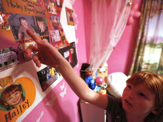 Hailey Byers, then 8, points to a picture of her father, Casey Byers, serving in Iraq. Hailey never met her father, who was killed in action. She's now being raised by his parents, Bill and Ann Byers. Photographs in her bedroom keep the memory of her father vivid.