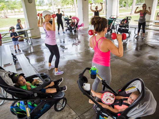 """Corbin Williams, 1, left, and Cooper Emens, 1, right, sit in their strollers while their mothers workout during a """"Stroller Moms"""" workout at Vineyards Park on Tuesday, May 22, 2018."""