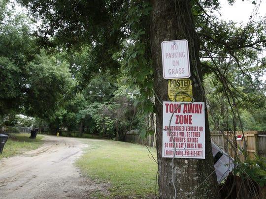 Warning signs hang around the tress on Moon Lane. Neighbors