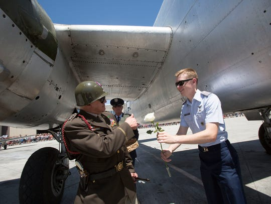 Veterans place carnations into a B-25 bomber that would