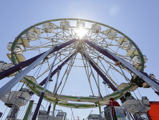 People ride on a Ferris wheel Friday during the Lincoln