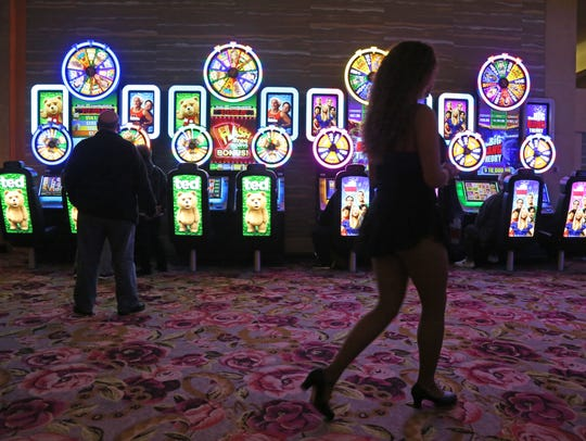 A cocktail waitress walks past the slot machines at