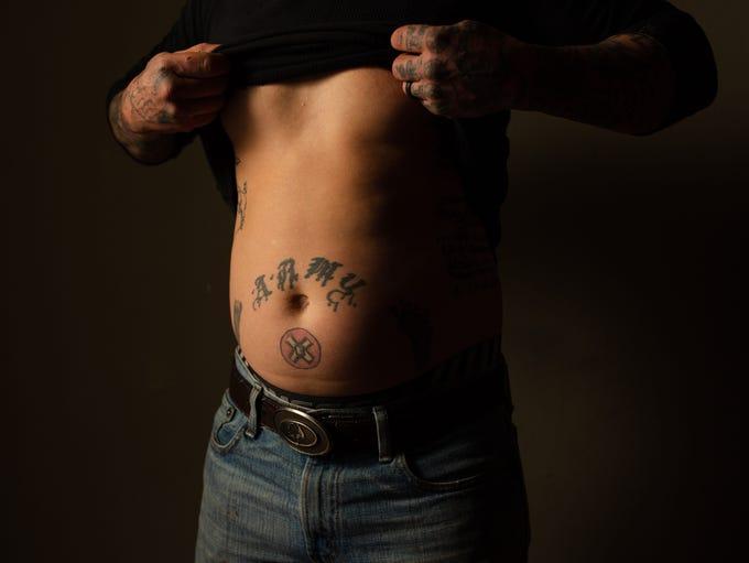 A KKK symbol is tattooed below Chris Buckley's navel.