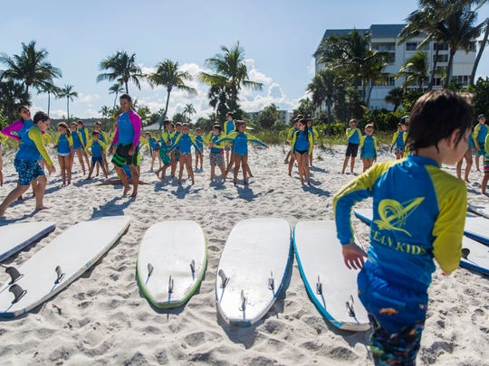 Ocean Kids summer camp members line up for stretches on Lowdermilk Beach before the start of activities on Wednesday, June 6, 2018.
